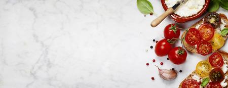 Paradicsommal és bazsalikommal szendvics összetevők - olasz, vegetáriánus vagy egészséges élelmiszer fogalmát Stock fotó