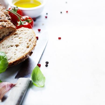 gıda: beyaz mermer zemin üzerine domates, ekmek, fesleğen ve zeytinyağı. İtalyan yemek, sağlıklı gıda ya da vejetaryen kavramı
