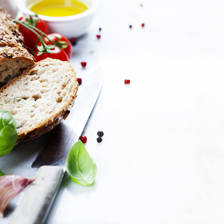 Tomato, bread, basil and olive oil on white marble background. Italian cooking, healthy food or vegetarian concept Stockfoto