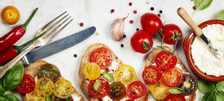 picada: Tomate y albahaca bocadillos con ingredientes - italiano, concepto Comida vegetariana o saludable Foto de archivo