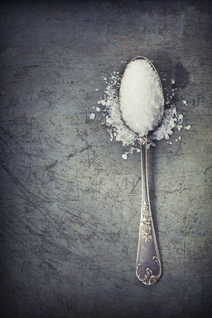 spoons: silver spoon filled with salt on rustick background Stock Photo