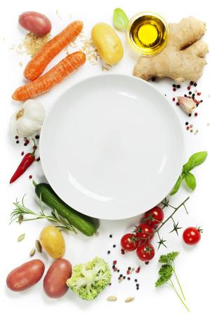 liggande: Färska grönsaker runt tom vit platta, ovanifrån, kopiera utrymme