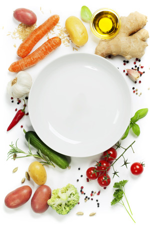 Fresh vegetables around empty white plate, top view, copy space