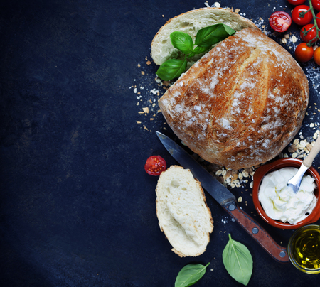 dark backgrounds: Homemade bread loaf and fresh ingredients for making sandwiches (tomatoes, basil, olive oil, cream cheese) on rustic dark background. Cooking, Healthy or vegetarian eating concept. Background layout with free text space.