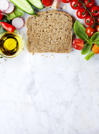 haciendo pan: Slice of a whole wheat bread and healthy organic vegetables for making sandwiches. Healthy eating or cooking concept.Background layout with free text space. Foto de archivo