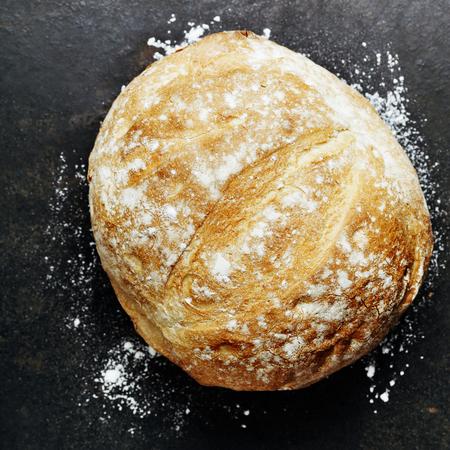 pan frances: Hogaza de pan hecho en casa en rústica fondo oscuro