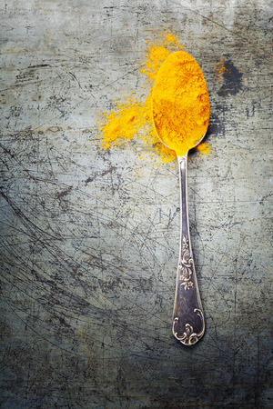 curry powder: Bright spices, spilled curry powder and spoon on rustic metal background