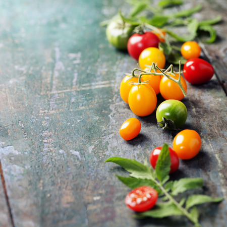 heirloom: various of colorful tomatoes on wooden background. Cooking, Healthy Eating or Vegetarian concept.  Background layout with free text space.