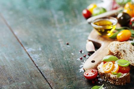 トマトとバジルのサンドイッチ成分とイタリア語、ベジタリアンや健康食品のコンセプト。 フリー テキスト スペースの背景のレイアウト。
