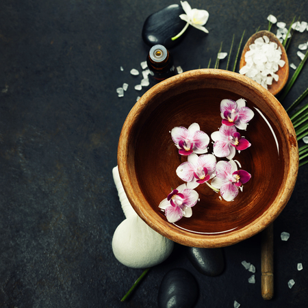 stone bowl: Close up of flowers floating in bowl of water and SPA setting Stock Photo