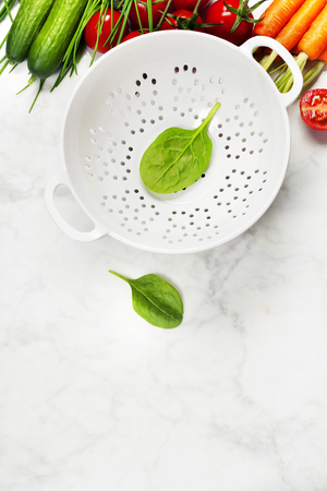 cooking oil: fresh organic garden vegetables and colander bowl on white rustic stone background, healthy cooking concept