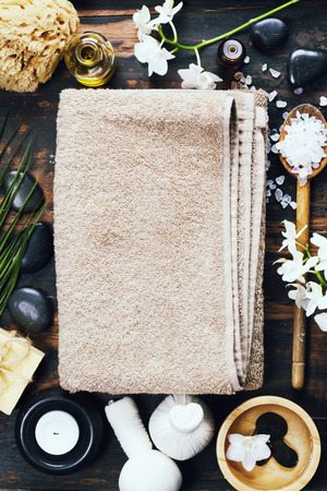 scincare: Spa background (white orchid, herbal compress stamps, sea salt, towel, candle and massage stones)