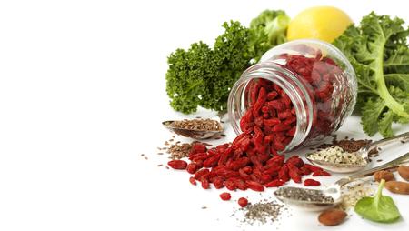 Различные суперпродуктов на белом фоне. Здоровое питание, диеты, вегетарианское или чистой питания концепции. Фон макета с бесплатным пространством текста. Фото со стока