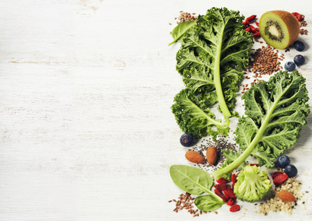 Healthy green smoothie or salad ingredients on white - superfoods, detox, diet, health or vegetarian food concept. Background layout with free text space.