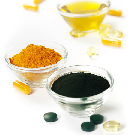 dietary supplements: Alternative natural medicine. Dietary supplements. Spirulina, turmeric  and organic oil on white background. Superfood, detox or diet concept