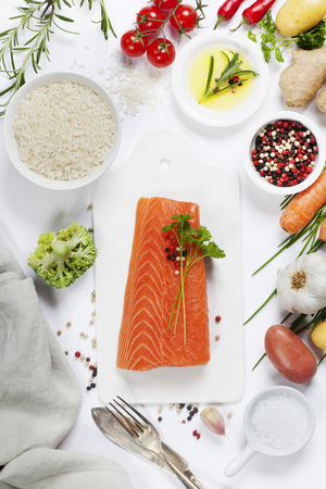 cocina saludable: Delicious portion of fresh salmon fillet with aromatic herbs, spices and vegetables - healthy food, diet or cooking concept. Top view.