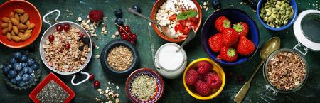 Café da manhã saudável do muesli, bagas com iogurte e sementes no fundo escuro - alimento saudável, dieta, desintoxicação, conceito limpo comer ou de vegetariano.