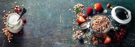 plato de comida: Desayuno saludable de muesli, bayas con yogur y semillas sobre fondo oscuro - La comida sana, dieta, desintoxicación, comer limpio o concepto vegetariano.