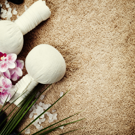 scincare: Spa background (pink orchid, herbal compress stamps, sea salt, towel and massage stones)