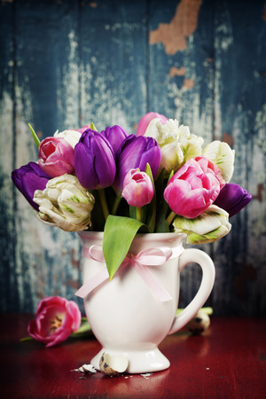 tulips in vase: Beautiful tulips bouquet on old wooden table Stock Photo