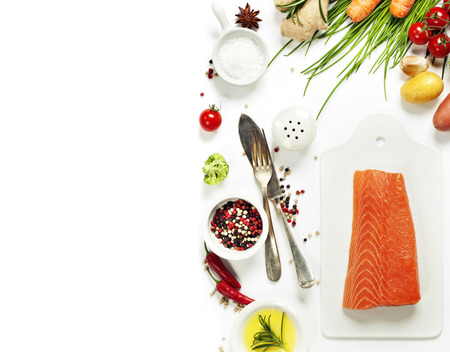 Delicious portion of fresh salmon fillet with aromatic herbs, spices and vegetables - healthy food, diet or cooking concept. Top view.