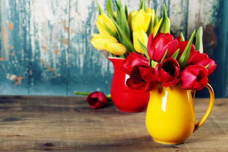 flowers in vase: Spring tulips in vases  on wooden table - spring, easter or gardening concept