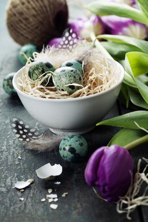 arreglo floral: Composición de Pascua con los tulipanes, los huevos y la jerarquía en el fondo de madera de época