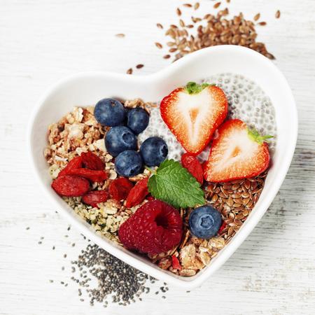 Gezond ontbijt van muesli, bessen met yoghurt en zaden op witte achtergrond - Gezonde voeding, dieet, Detox, Clean eten of vegetarisch concept.Top view Stockfoto