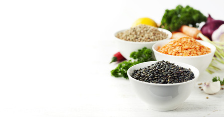 variety: Bowls of assorted dried lentils with vegetables over white