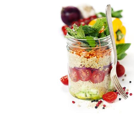 Komkommer, quinoa, tomaat, ui, wortel en munt salade in een pot over wit