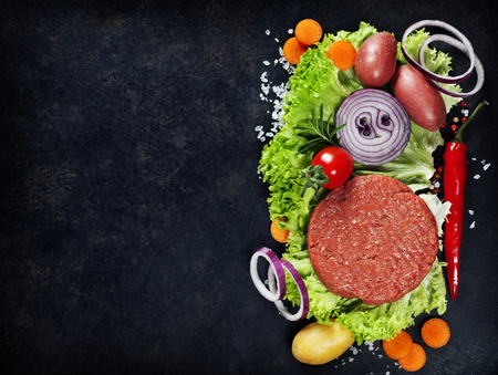 Raw Ground beef meat Burger steak cutlets with seasoning and vegetables on vintage  board