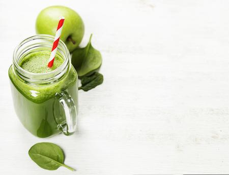 batidos de frutas: licuado saludable verde y los ingredientes en blanco - súper alimentos, desintoxicación, la dieta, la salud, el concepto de la comida vegetariana