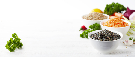 protein crops: Bowls of assorted dried lentils with vegetables over white