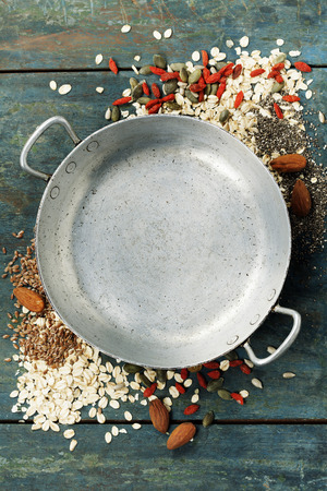 detoxing: Healthy breakfast composition with space for text - oats, goji berries, banana, nuts, pumpkin and chia seeds around old empty cooking pot on rustic wooden background, top view composing Stock Photo