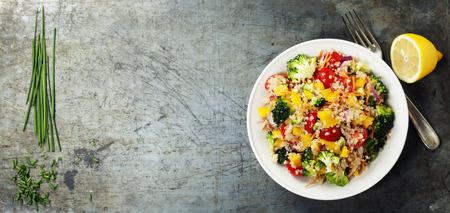 ブロッコリー、ピーマン、ニンジン、タマネギ、無作法な金属背景にトマトとキノアのサラダ。スーパー フードの概念。