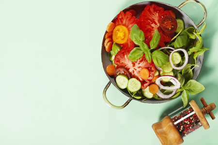 Fresh salad on blue background - Tomatoes, onion, carrot, basil, cucumbers, salt and pepper. Top view