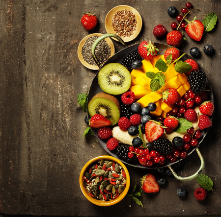 superfood: fresh summer fruits and berries on plate, above, rustic background