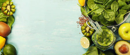 Gezonde groene smoothie en ingrediënten op een blauwe achtergrond - superfoods, detox, dieet, gezondheid, vegetarisch voedsel concept Stockfoto