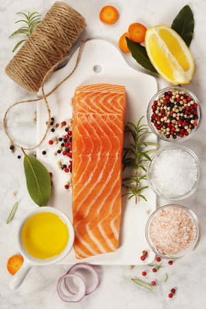 Salmon: Delicious portion of fresh salmon fillet with aromatic herbs, spices and vegetables - healthy food, diet or cooking concept. Top view.