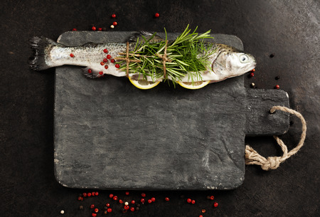 alimentos congelados: Raw rainbow trout with lemon, herbs and spice on rustic background