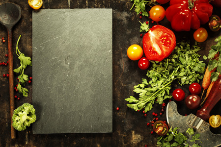 carte: Wooden spoon and ingredients on dark background. Vegetarian food, health or cooking concept.