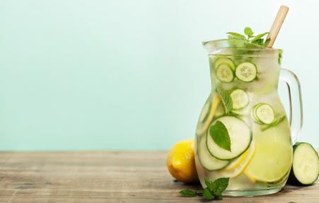 Água infundida com pepino, limão, lima e hortelã no fundo azul Imagens