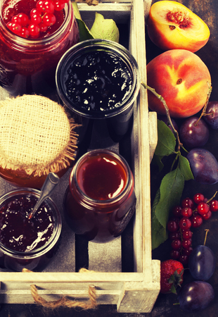 tastes: Fruit and berry jam and pieces of fruit tart on a rustic background Stock Photo
