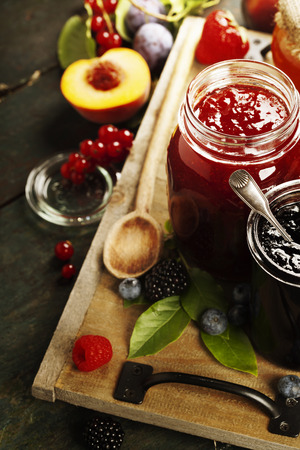 preserve: Fruit and berry jam with ingredients on a wooden background