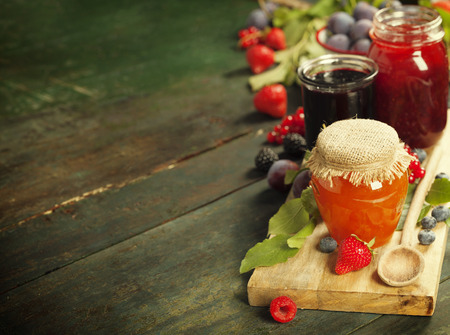 blueberry jam: Fruit and berry jam with ingredients on a wooden background