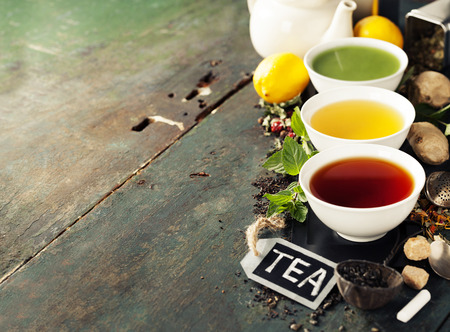 Tea concept. Different kinds of tea (black, green and matcha tea) in ceramic bowls and ingredients on wooden background