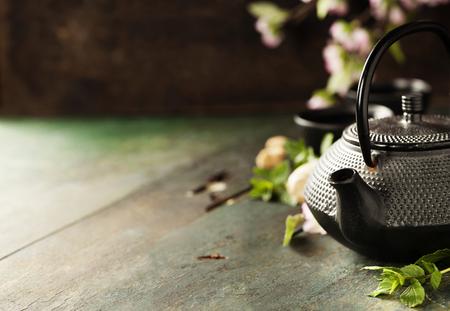 Tea concept, kopjes met thee en traditionele theepot versierd met bloeiende lente boomtak