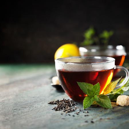 Heiße Tasse Tee mit Minze und Zucker auf rustikalen Hintergrund