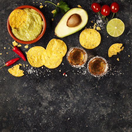 shot: Bowl of mexican nachos chips with homemade fresh guacomole sauce and tequila shots over old  background. Top view. With space for text Stock Photo