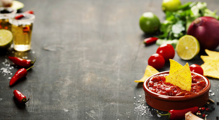 NACHO: Fresh salsa dips with nachos chips and ingredients on old background. Space for text Stock Photo